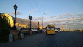 Gele bus op de dijk van Riga met de beroemde lokale markt royalty-vrije stock foto's
