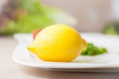 Gele citroen op een witte plaat met andere groenten Royalty-vrije Stock Fotografie