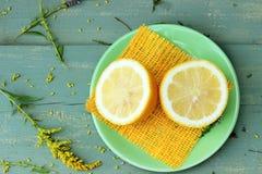 Gele citroen op groene houten lijst met sommige bloemendetails Stock Afbeeldingen