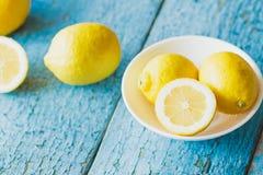 Gele citroenen in de witte plaat, houten achtergrond Royalty-vrije Stock Afbeeldingen
