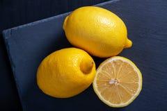 Gele citroenen op een zwarte achtergrond royalty-vrije stock afbeeldingen