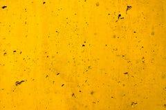 Gele concrete muur ruwe die voorgevel van natuurlijk cement met gaten en onvolmaaktheden als lege rustieke textuurachtergrond wor stock foto