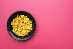 Gele cornflakes in een zwarte plaat op een roze achtergrond Plaats voor de tekst royalty-vrije stock afbeeldingen