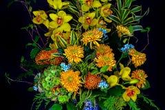 Gele cymbidiumorchideeën en mums in bloempot royalty-vrije stock afbeelding