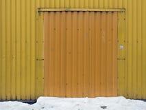 Gele de muurhulp van metaalstroken in het midden van het donkere gele vierkante openen onder de poort, geel tot geel, de bodem va Stock Fotografie