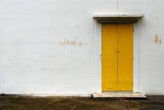 Gele deur op witte muur Stock Afbeeldingen