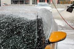 Gele die auto bijna helemaal in shampooschuim, met meer wordt behandeld royalty-vrije stock foto