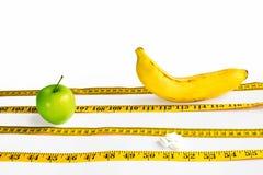 Gele die centimeterband als sportensporen wordt opgemaakt waarop groene die Apple concurreer, schillen en banaan op witte achterg stock foto