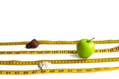 Gele die centimeterband als sportensporen wordt opgemaakt waarop groene die Apple concurreer, schillen en chocolade op witte acht stock afbeeldingen