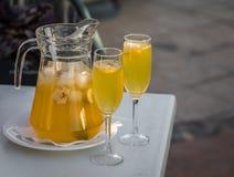 Gele die champagnesangria in een mok met twee glazen wordt gediend stock foto's