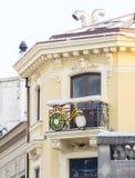 Gele die fiets op een balkon van een oud gebouw wordt opgeschort Stock Foto's