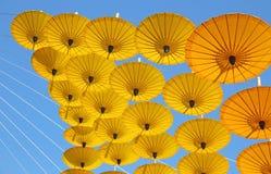 Gele document paraplu die in de blauwe hemel drijven Royalty-vrije Stock Afbeelding