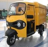 Gele driewielerbestelwagen bij Stock Foto