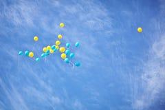 Gele en blauwe ballons in de hemel Royalty-vrije Stock Foto's