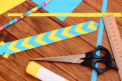 Gele en blauwe referentie van gevouwen document De schaar, lijmstok, kleurde document bladen, heerser, potlood op een bureau Eenv Stock Foto's