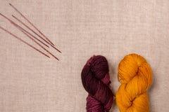 Gele en donkerrode lange draden die als draad van het koordpak voor het naaien rolden Stock Fotografie