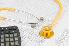 Gele en gouden stethoscoop met calculator Stock Foto's