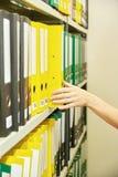 Gele en groene dossieromslagen in archief en menselijke hand stock foto