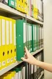 Gele en groene dossieromslagen in archief en menselijke hand royalty-vrije stock foto's