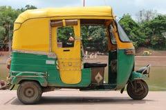 Gele en groene Indische autoriksja Gele en groene tuktuk dichtbij rivier stock foto
