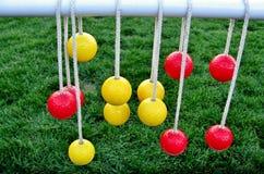 Gele en rode ballen die op rops hangen Stock Afbeelding