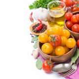 Gele en rode kersentomaten in kom, olijfolie en kruiden Royalty-vrije Stock Foto