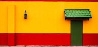 Gele en rode muur met een straatlantaarn stock fotografie