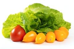Gele en rode tomaten en saladeromano op een witte achtergrond stock foto
