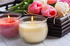 Gele en roze aromakaarsen met tulpen Royalty-vrije Stock Fotografie