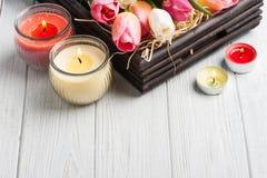 Gele en roze aromakaarsen met tulpen Royalty-vrije Stock Foto's