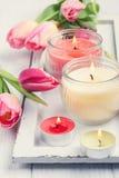 Gele en roze aromakaarsen met tulpen Stock Foto