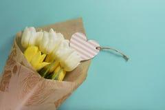 Gele en witte tulpen met hartkaart in verpakkend document op een lichte turkooise achtergrond Stock Afbeelding