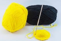 Gele en zwarte garenballen met haaknaald Stock Afbeeldingen
