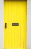 Gele geschilderde houten deur met brievenbus en handvat Royalty-vrije Stock Foto