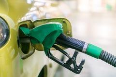 Gele, gouden auto bij een benzinestation die met brandstof worden gevuld stock fotografie