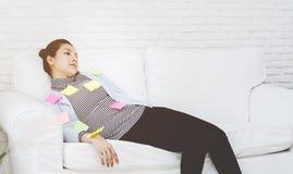 Gele, groene en roze document bladen op de vrouw die en uitgeput van het werk slaapt stock afbeelding