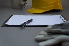 Gele helm, bouwvakker, notitieboekje, pen en handschoenen op grijze lijst Stock Afbeeldingen