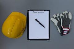 Gele helm, bouwvakker, notitieboekje, pen en handschoenen op grijze lijst Royalty-vrije Stock Foto