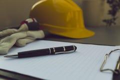 Gele helm, bouwvakker, notitieboekje, pen en handschoenen op grijze lijst Royalty-vrije Stock Fotografie