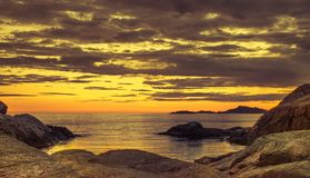 Gele hemel door het overzees na zonsondergang in Lindesnes in Noorwegen royalty-vrije stock foto's