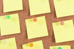 Gele herinnerings kleverige nota over cork raad Stock Afbeelding