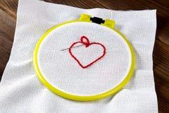 Gele hoepel voor borduurwerk met canvas en rode draden op het lijstclose-up, hart royalty-vrije stock foto's