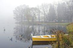 Gele houten boot op de herfstmeer en ochtendmist Royalty-vrije Stock Afbeeldingen