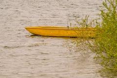 Gele houten boot op drift in meer Stock Foto