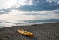Gele kano op een zandig strand dichtbij aan het overzees Stock Afbeeldingen