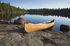 Gele kano op rotsachtige kust van kalm meer met pijnboombomen royalty-vrije stock afbeeldingen