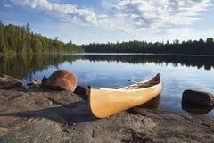 Gele kano op rotsachtige kust van kalm meer met pijnboombomen stock foto's