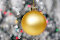 Gele Kerstmisbal tegen verre lichten Royalty-vrije Stock Afbeeldingen