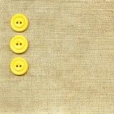Gele knopen op beige stof Royalty-vrije Stock Foto