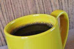 Gele koffiekop op houten achtergrond Royalty-vrije Stock Afbeeldingen